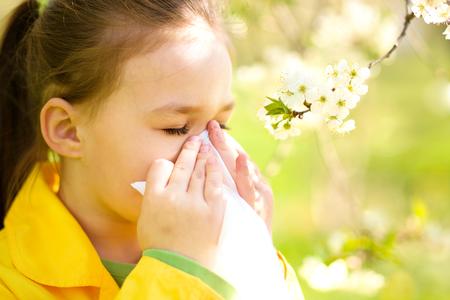 tosiendo: La niña está soplando su nariz cerca del árbol de la primavera en flor