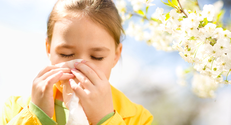 Little girl is blowing her nose near spring tree in bloom Banque d'images