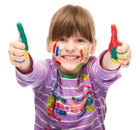 cool kids: Portrait of a cute girl playing with paints and showing thumb up sign using both hands, isolated over white Stock Photo