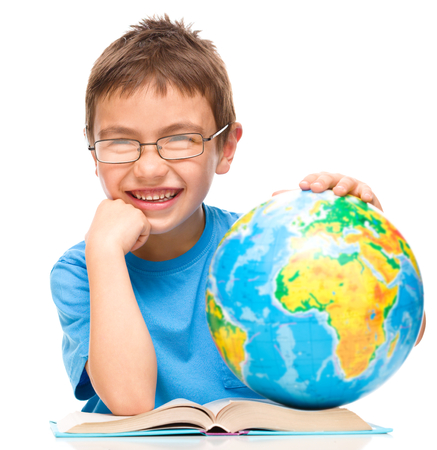 Little boy is examining globe while sitting at table, isolated over white photo