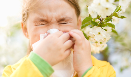 Little girl is blowing her nose near spring tree in bloom photo