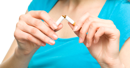 Young woman is breaking a cigarette, quit smoking concept, isolated over white photo