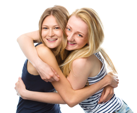two women hugging: Two young women are hugging as a best friends, isolated over white