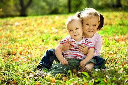 niños jugando en el parque: Niños lindos están jugando en el otoño de parque