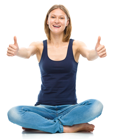 Young happy woman is sitting on the floor and showing thumb up sign using both hands, isolated over white photo