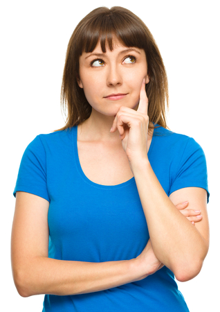 Portrait of a happy young woman thinking about something while touching her cheek with finger, isolated over white Stock Photo