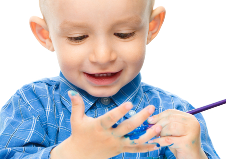 fingerpaint: Portrait of a cute little boy playing with paints, isolated over white