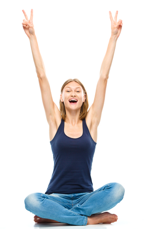 Young happy woman is sitting on the floor and showing victory sign using both hands, isolated over white