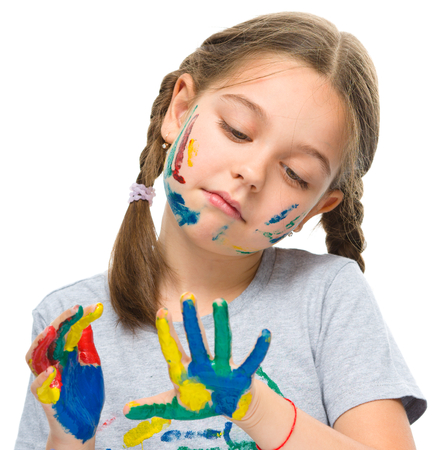 playschool: Portrait of a cute girl looking at her hands painted in bright colors, isolated over white