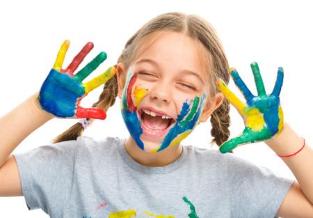 niños jugando en la escuela: Retrato de una muchacha linda que muestra sus manos pintadas de colores brillantes, aislados en blanco Foto de archivo