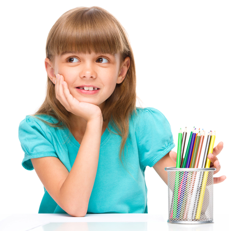 Portrait of a little girl holding color pencils supporting her head with hand, isolated over white