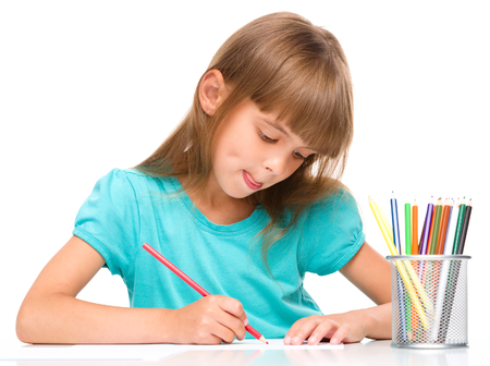 sticking: Little girl is drawing using color pencils while sitting at table and sticking her tongue out, isolated over white