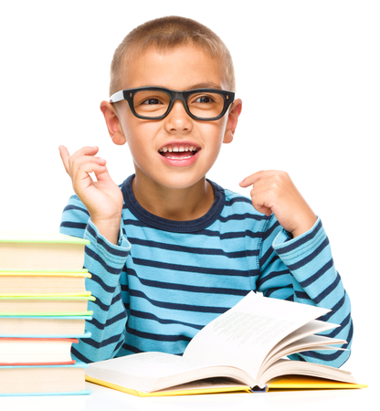 elementary students: Young boy is daydreaming while reading book and wearing glasses, isolated over white