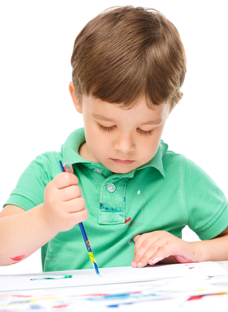 Portrait of a cute little boy playing with paints, isolated over white photo