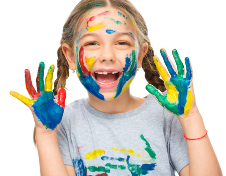 nursery school: Portrait of a cute girl showing her hands painted in bright colors, isolated over white