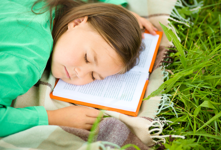 drowse: Little girl is sleeping on her book outdoors