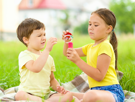 Little girl and boy are blowing soap bubbles, outdoor shoot photo