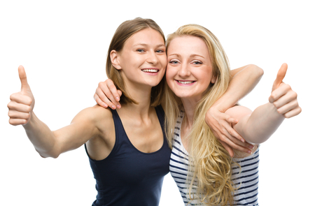 thumbs up sign: Two young happy women are hugging and showing thumb up sign, isolated over white
