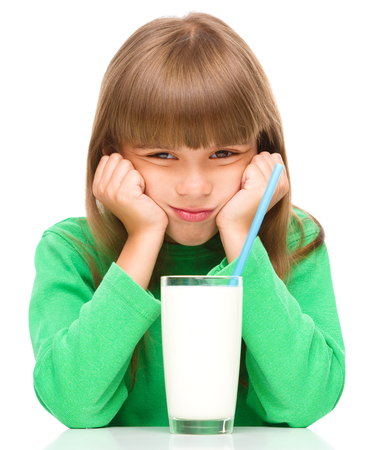 Gloomy little girl does not want to drink milk, isolated over white photo