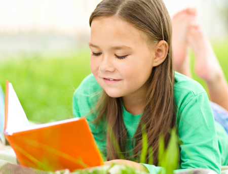 one story: Cute little girl is reading a book while laying on green grass
