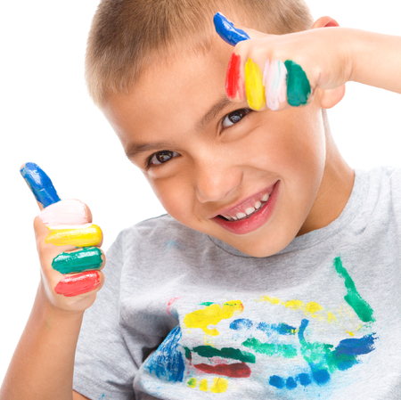 fingerpaint: Portrait of a cute boy playing with paints and showing thumb up sign using both hands, isolated over white