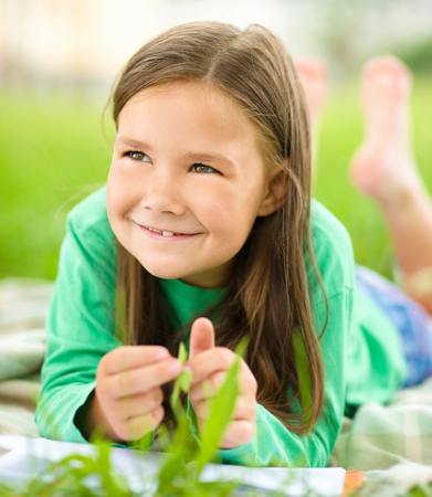 Portrait of a little girl laying on green grass, outdoor shoot Stock Photo - 30424082