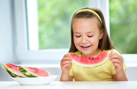 Cute little girl is eating watermelon, isolated over white Stock Photo - 30424083