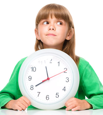 Little girl is holding big clock, isolated over white photo