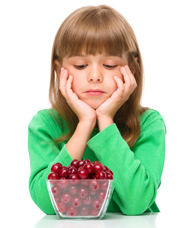 resist: Cute girl doesnt want to eat cherries, isolated over white