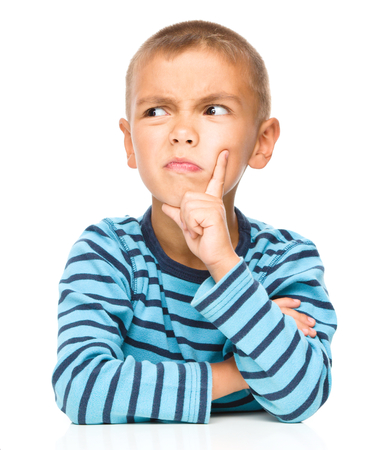 Portrait of a suspicious little boy touching his cheek with index finger, isolated over white