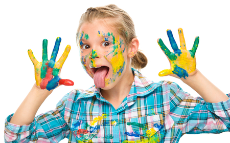 Portrait of a cute girl showing her hands painted in bright colors and sticking tongue out, isolated over white photo