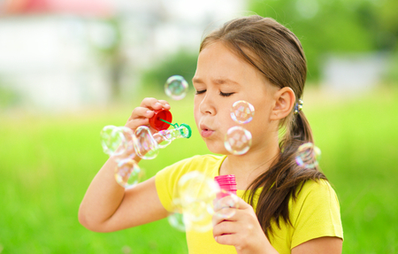 Cute little girl is blowing a soap bubbles Stock Photo - 30606910