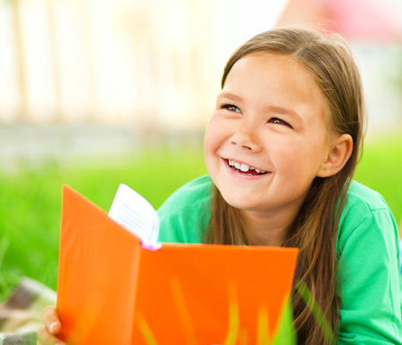 Cute little girl is reading a book while laying on green grass Stock Photo - 30606913