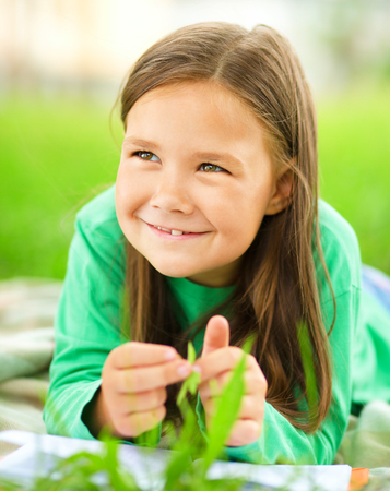 Portrait of a little girl laying on green grass, outdoor shoot Stock Photo - 30606914