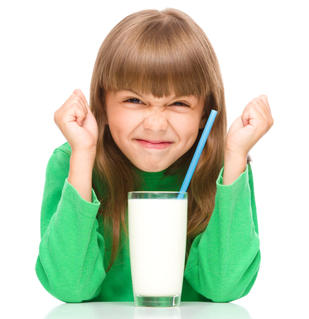 disobey: Little girl with a glass of milk, isolated over white Stock Photo