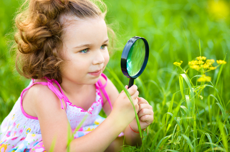 Young girl is looking at flower through magnifier, outdoor shoot Banque d'images