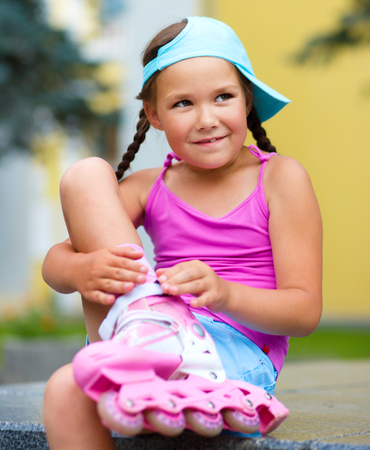 rollerskating: Little girl is wearing roller-blades in city park Stock Photo