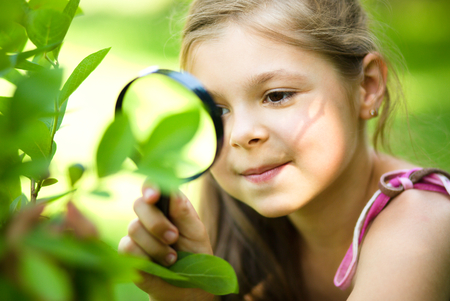 Young girl is looking at tree leaves through magnifier, outdoor shoot