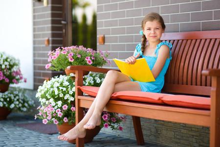 La petite fille mignonne est en train de lire un livre alors qu'il était assis sur le banc