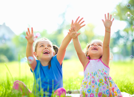 Two little girls are catching soap bubbles, outdoor shoot