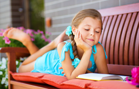 elementary students: Cute little girl is reading a book while laying on bench