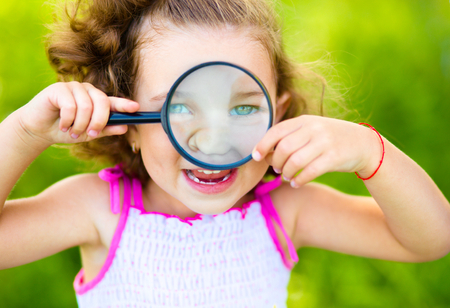Little girl is looking through magnifier, outdoor shoot photo
