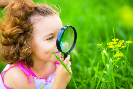 Young girl is looking at flower through magnifier, outdoor shoot Stock Photo