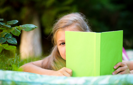 Little girl is hiding behind book while laying on green grass photo
