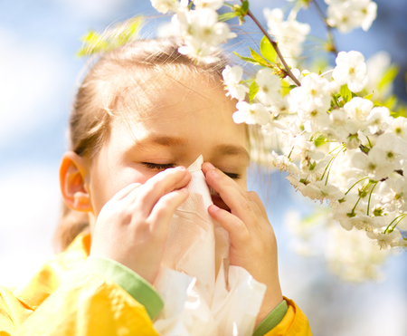 Little girl is blowing her nose near spring tree in bloom Imagens
