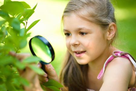 Jong meisje is op zoek naar boombladeren door vergroot, outdoor shoot