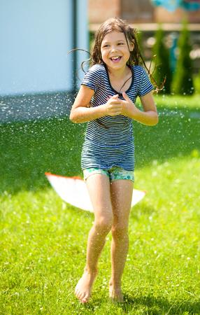 sotto la pioggia: La ragazza felice sta giocando sotto la pioggia su cortile