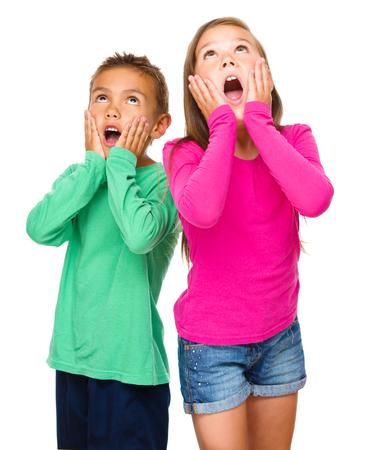 astonishment: Ni�a y ni�o son la celebraci�n de sus caras de asombro mientras mira hacia arriba, aislado m�s de blanco