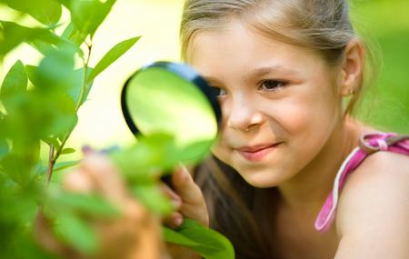 La chica joven está mirando las hojas del árbol a través de la lupa, lanzamiento al aire libre