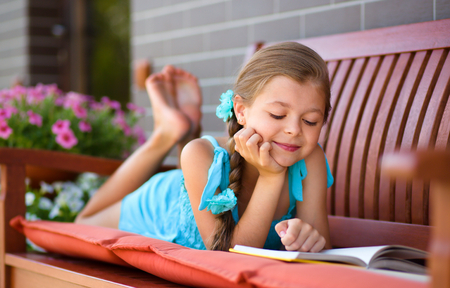 girl reading book: Cute little girl is reading a book while laying on bench